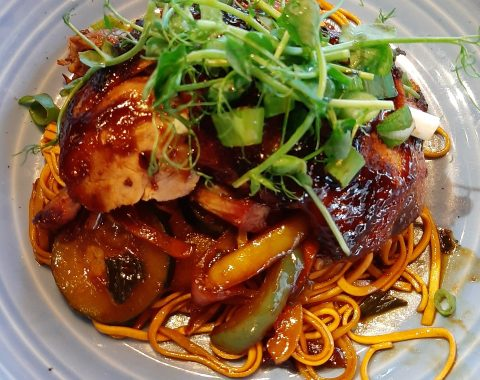 Hoisin Glazed Half Roast Duck, served on a bed of Stir-Fried Vegetables and Fine Noodles, with Honey and Soy Sauce